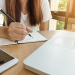 white woman writing with a pencil in a notebook