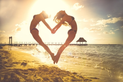 two bikini clad women on the beach forming a heart shape with their bodies