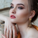 head shot of white woman with gold chandelier earrings