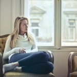 blond woman sitting on sofa looking out window thoughtfully