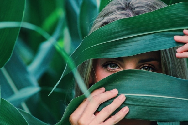 woman peeking through large leaves