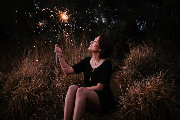 smiling woman holding sparkler