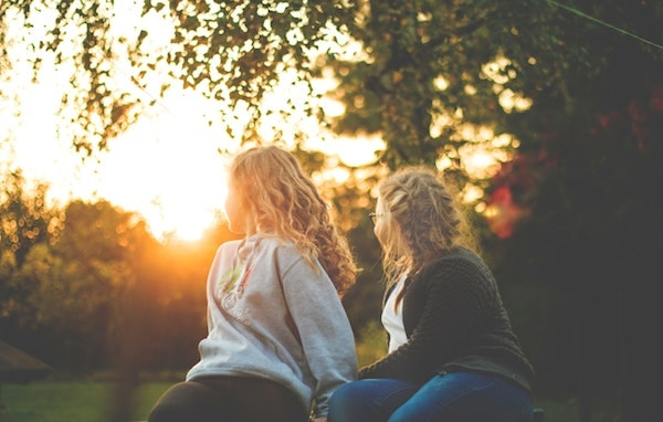 two young girls sitting in a park at sunset