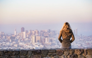 woman sitting alone on stone wall, gazing at cityscape