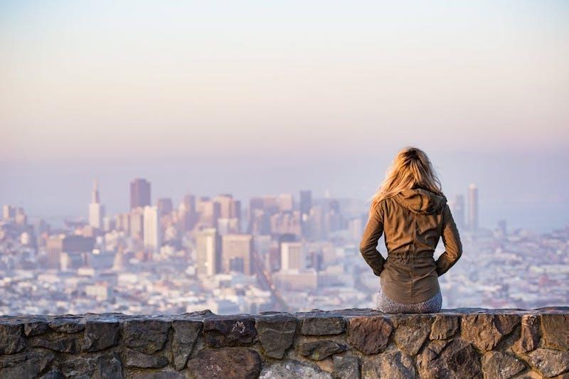 woman sitting alone on stone wall, gazing at cityscape