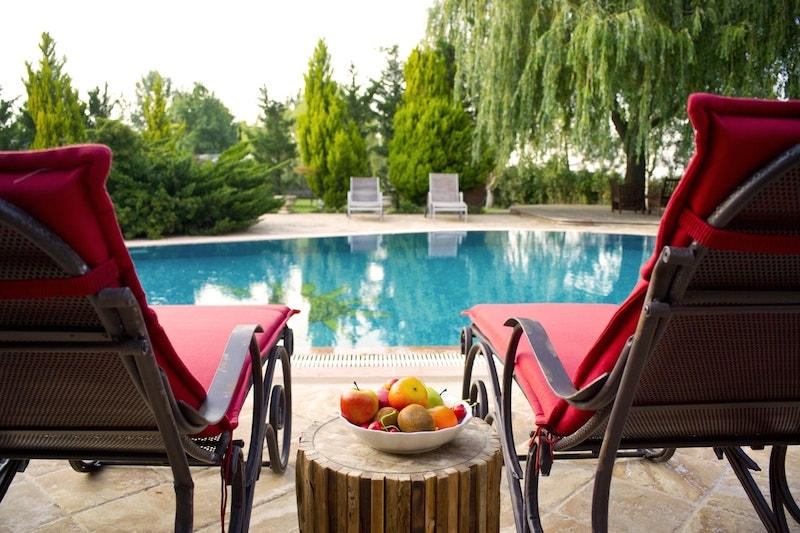 red poolside chairs with bowl of apples between them