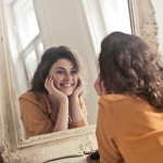 woman in orange blouse, smiling at her reflection