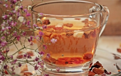 closeup of herbs and hot tea in a clear glass