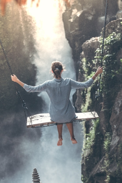 woman on swing above waterfall