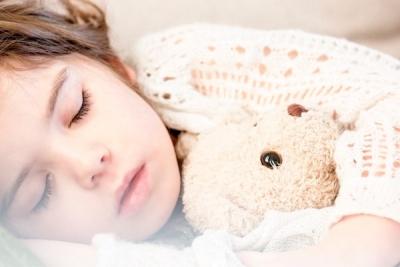 sleeping child holding teddy bear