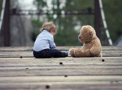 baby boy sitting on wood deck with stuffed bear