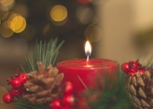 red candle decorated with holiday pine cones and berries