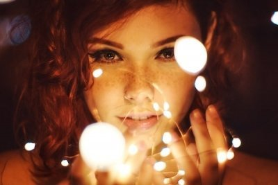 closeup of young red headed, freckled beautiful woman and orbs of light