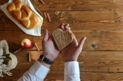aerial view of man's hands holding heart shaped slice of bread above wooden kitchen table