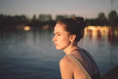 pensive anxious woman sitting near water at sunset